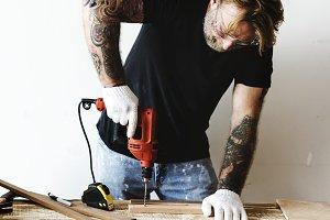 A carpenter using a drill