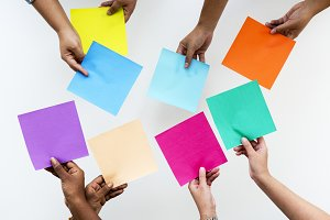 hands holding colorful square paper