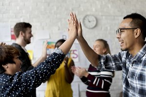 Colleagues hi-five in the office
