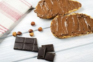 Chocolate spread on bread, hazelnuts, napkin and chocolate tablet on wooden table. Copy space.