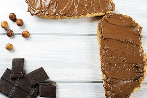 Chocolate spread on bread, hazelnuts and chocolate bar on wooden table. Copy space.