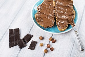 Chocolate spread on bread on a blue plate next to pieces of chocolate, knife and hazelnuts on wooden table.
