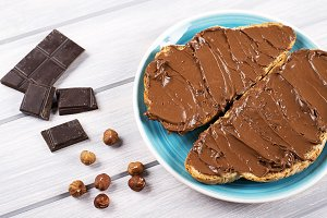 Chocolate spread on bread on a blue plate next to pieces of chocolate and hazelnuts on wooden table.