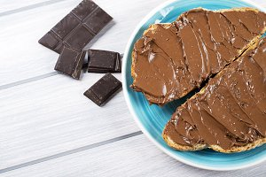Chocolate spread on bread on a blue plate next to pieces of chocolate on wooden table. Copy space.