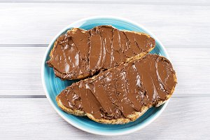 Chocolate spread on bread on a blue plate on wooden table.