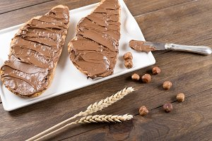Bread with chocolate spread on brown wooden table next to a knife, hazelnuts and wheat flower. Food.