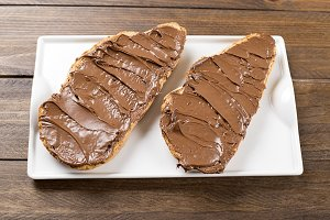 Chocolate spread on bread on a plate over brown wooden table. Food.