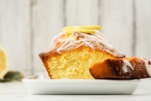 Lemon loaf with white glaze on wooden background