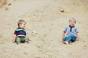Two little boys on sand beach at the lake.