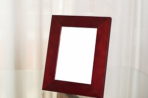 Wooden photo frame on glass table. Portrait.