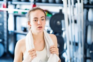 Young woman in gym, towel around her neck, resting