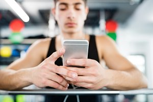 Hispanic man in gym resting, holding smart phone,listening music