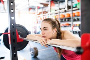 Young woman in gym, earphones in her ears,listening music