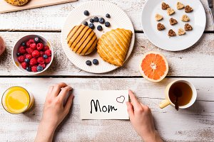 Mothers day composition. Little note and breakfast meal.