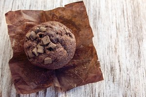 chocolate muffin on white wooden bac