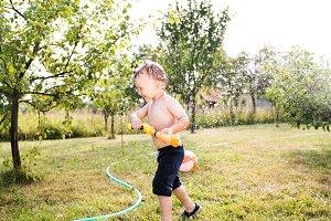 Little boy with water gun splashing somebody, sunny summer garde