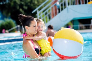 Mother with her daughter in swimming pool. Sunny summer.