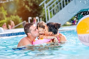 Mother, father kissing daughter in swimming pool. Sunny summer.