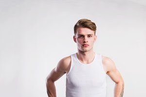 Young handsome hipster man in white vest, studio shot.