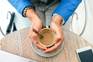Hands of businesswoman holding a cup of coffee