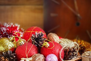 Christmas Composition with Gifts. Basket, red balls, pine cones, snowflakes on Wooden Table. Vintage style