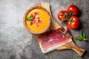 Spanish tomato soup Salmorejo served in olive wooden bowl with ham jamon serrano on stone background. Top view, copy space