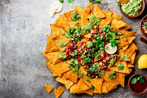 Nachos. Totopos with sauces. Mexican food concept. Yellow corn totopos chips with different sauces salsas - pico del gallo, guacamole, salsa verde, chili pebre. Copy space on stone gray background, top view