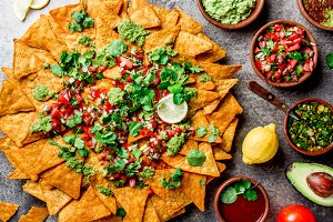 Nachos. Totopos with sauces. Mexican food concept. Yellow corn totopos chips with different sauces salsas - pico del gallo, guacamole, salsa verde, chili pebre and fresh avocado, tomatoes, lemon and cilantro on stone gray background, top view