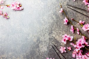 Chopsticks and sakura branches on gray stone background. Japanese food concept. Top view, copy space.