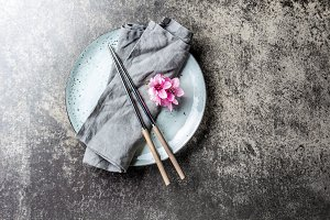 Chopsticks and sakura flowers on gray plate, stone background. Japanese food concept. Top view, copy space.