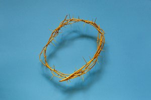 Yellow crown of thorns on a blue background, top view. religion worship tradition symbols concept