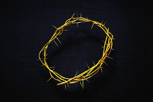 Yellow crown of thorns on a black background, top view. religion worship tradition symbols concept