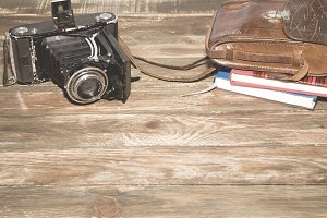 Old camera, notebooks on vintage wood background