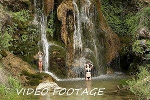 Sisters bathing under a waterfall