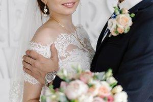 Groom gently hugging smiling bride