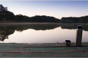 Thermos on a wooden pier by the lake. Morning coffee by the lake.
