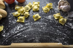 Raw ravioli on black background