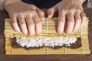 Woman making sushi rolls
