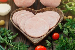 Cutted Ham Sausage in heart plate on wooden background