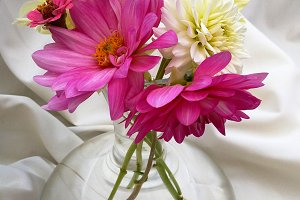Glass with dahlias bouquet