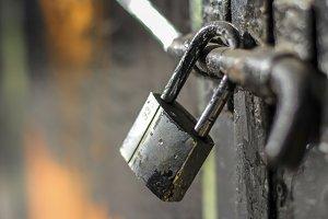 Closed black padlock in a door
