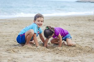 Two kids digging on the beach