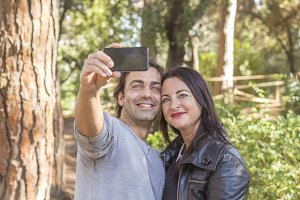 Couple taking a selfie in woods