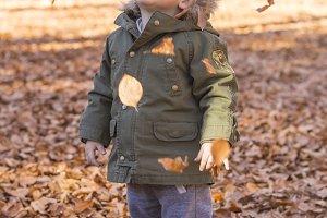 Cute baby seeing falling leaves