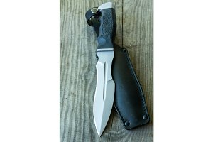 A large army knife with a leather case. Vertical shot.