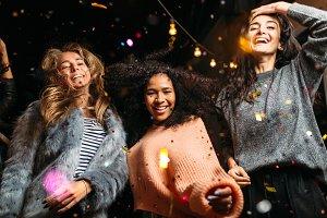 Female friends dancing with confetti