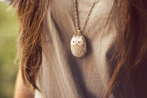 Woman wearing owl necklace.