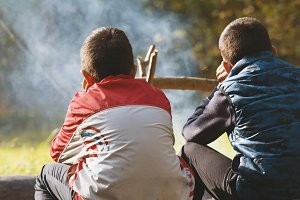 Two boys teenagers in camping seat near campfire