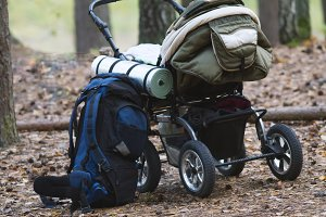 Baby stroller and camping backpack in autumn forest