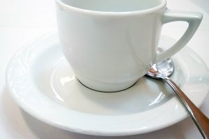 White coffee porcelain cup and saucer stands on a table